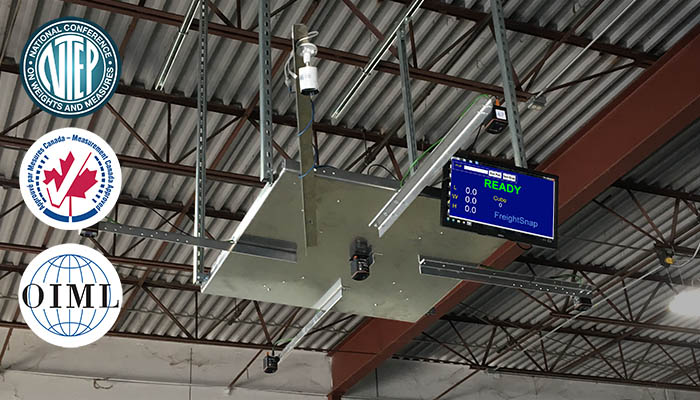 FreightSnap's FS 5000 pallet dimensioner hanging from a tall warehouse ceiling. NTEP, Measurement Canada, and OIML certification logos are also pictured.