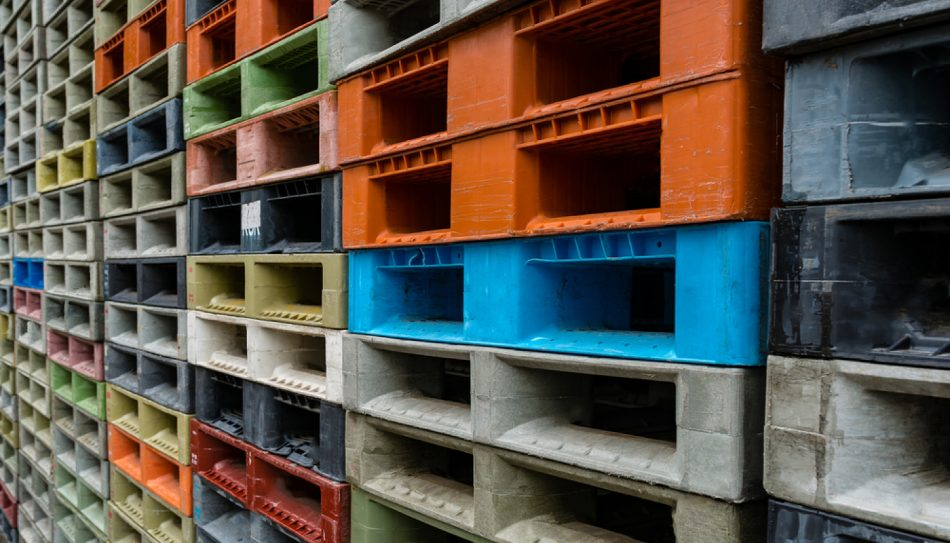 Tall stacks of multi-colored plastic shipping pallets.