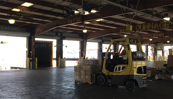 A forklift operator using FreightSnap's FS 5000 pallet dimensioner at a trucking terminal.