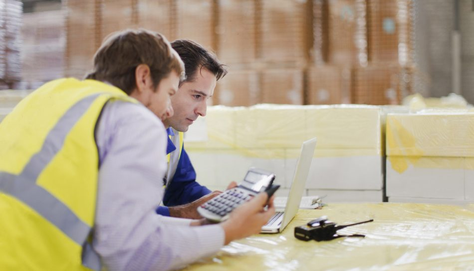 Two men comparing shipping costs at a computer inside a warehouse.