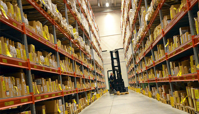 A forklift operator driving down a fully stocked warehouse aisle.