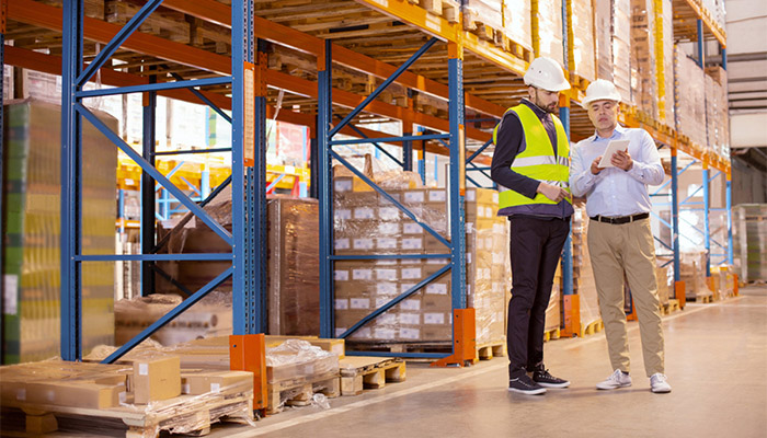 Two men discussing inventory inside a shipping warehouse.